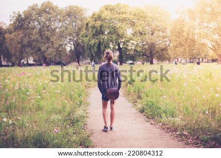 A young woman is standing amongst flowers in a meadow - stock photo