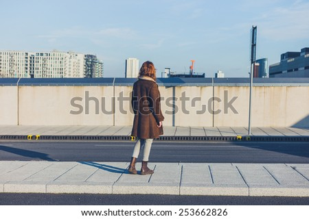 A young woman is standing in the road and is looking at the skyline of a city in the winter - stock photo
