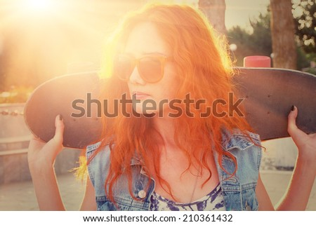 A young woman is standing in the street holding skateboard behind her head. Joyful feelings. Outdoors, street fashion lifestyle. Beautiful young woman with a skate - stock photo