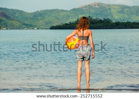 A young woman is standing on a tropical beach with a beach ball - stock photo