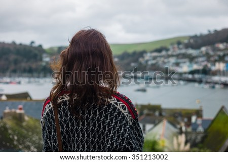 A young woman is standing on top of a hill and is looking at an estuary with boats - stock photo