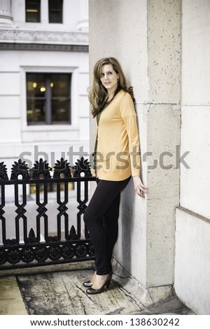 A young woman is standing outside a neighborhood and looking forward/Portrait of Young Woman - stock photo