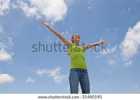 A young woman is standing outside with outstretched arms.  She is smiling and looking away from the camera.  Horizontally framed shot. - stock photo