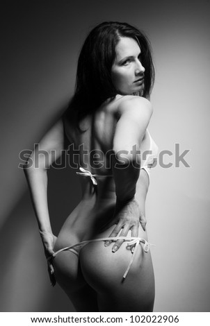 A young woman is taking her erotic lingerie off. She is standing back and looking over shoulder. The sexy girl is wearing a transparent bodysuit. - stock photo