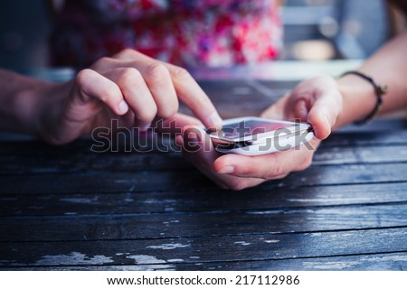 A young woman is using her smart phone at a table outside - stock photo