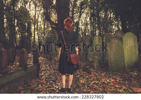 A young woman is walking amongst the tombstones in a cemetery - stock photo