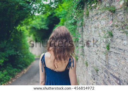 A young woman is walking by a wall in the countryside