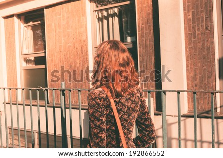 A young woman is walking in the city on a sunny day - stock photo