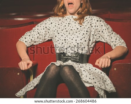 A young woman is watching a scary movie at the cinema - stock photo