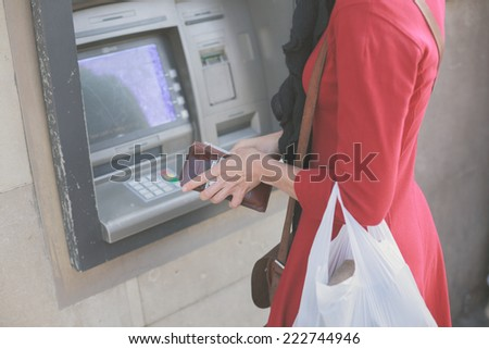A young woman is withdrawing money from an ATM - stock photo
