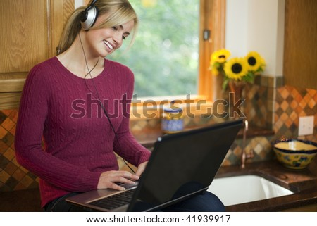 A young woman is working on a laptop in her kitchen.  She is wearing headphones, smiling, and looking away from the camera.  Horizontal. - stock photo