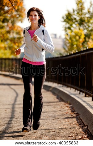 A young woman jogging on a path in a park - stock photo
