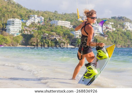 A young woman kite-surfer ready for kite surfing rides in blue sea - stock photo