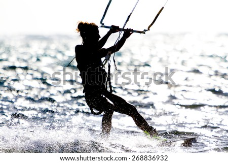 A young woman kite-surfer rides against the sun - stock photo
