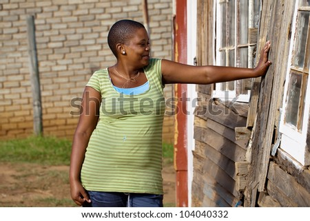 A young woman leaning against her shack in the townships. - stock photo