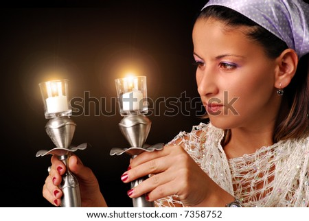 A young woman Lighting the candles for Jewish Sabbath, isolated on black - stock photo