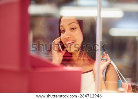 A young woman looking at a handbag through a shop window while talking on the phone - stock photo