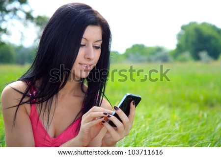 A young woman looking at phone and smiling