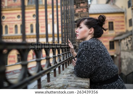 A young woman looking into the old building or factory through the iron fence with vintage ornament. - stock photo