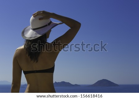 A young woman looks out across a sea view towards Greek islands. Bodrum, Turkey / woman with white hat - stock photo