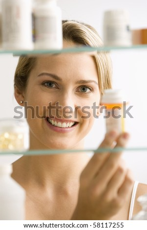 A young woman looks through a medicine cabinet and smiles at the camera.  Vertical shot.