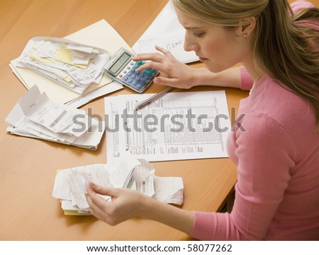 A young woman looks upset while sorting through her old receipts.  Horizontal shot. - stock photo