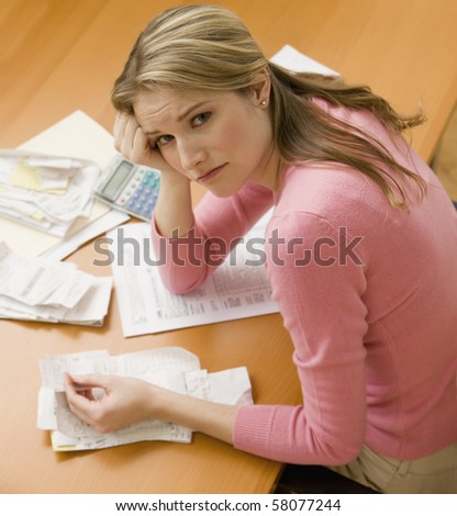 A young woman looks upset while sorting through her old receipts.  Square shot. - stock photo