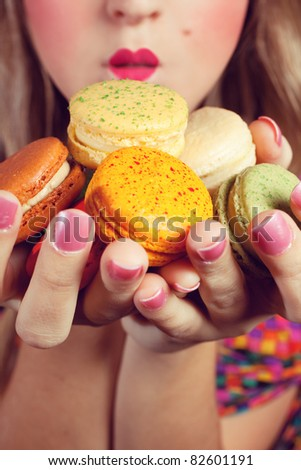 A young woman loves her sweet macaron. - stock photo