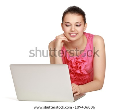 A young woman lying on the floor with a laptop, isolated on white background - stock photo