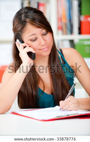 A young woman making notes whilst on the phone - stock photo