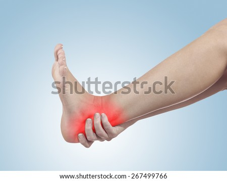 A young woman massaging her painful ankle. Medicine concept photo.