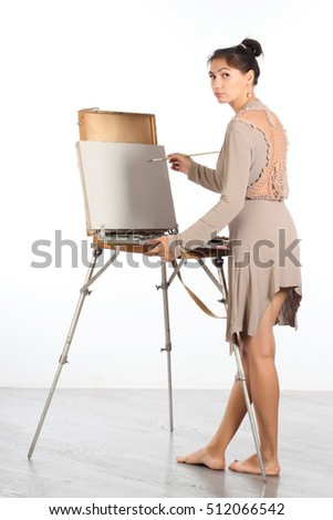 A young woman near easel begins to draw a picture.