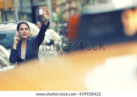 A young woman or businesswoman hailing a yellow taxi cab while talking on her cell phone in a New York City - stock photo
