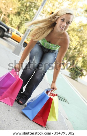 A young woman picking up her shopping bags. - stock photo