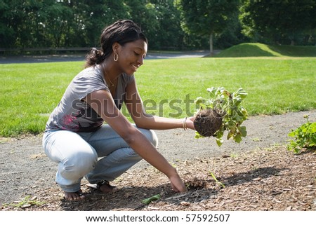 A young woman planting in her garden. - stock photo