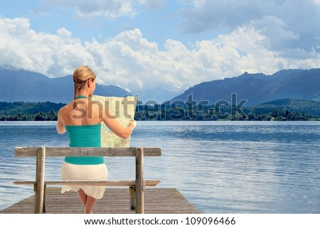 A young woman reading a map sitting on a bench in front of a lake - stock photo
