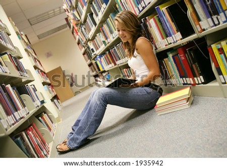 A young woman reading in the library - stock photo