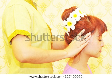 A young woman receiving a head massage in a spa
