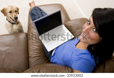 A young woman relaxes on the couch while on her laptop computer with her dog at her side - stock photo