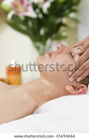 A young woman relaxing at a health spa while having a relaxing destressing head massage
