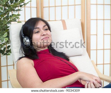 A young woman relaxing in a chair with headphones over her ears. - stock photo