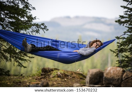 a young woman relaxing in a hammock  - stock photo