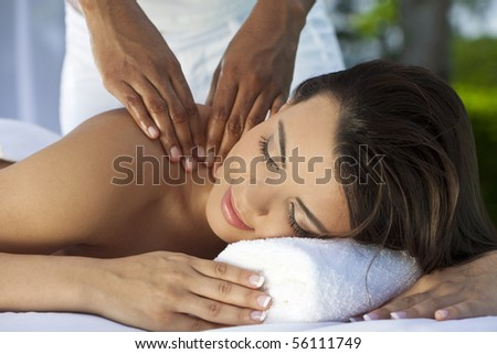 A young woman relaxing outside at a health spa while having a massage with a natural green background - stock photo