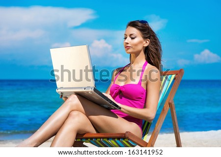 A young woman relaxing with a laptop on a beautiful beach - stock photo
