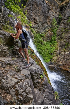 a young woman rock climbing next to a waterfall - stock photo