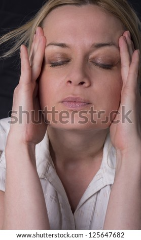 A young woman rubbing her temples to ease her pain - stock photo
