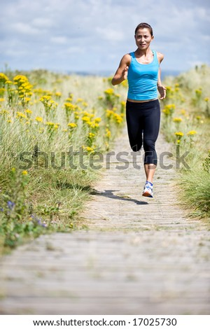 A young woman running in the countryside - stock photo