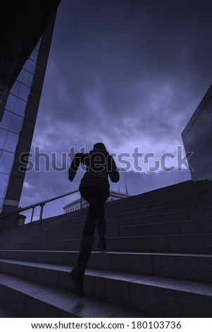 A young woman runs up city steps / woman running up city steps - stock photo