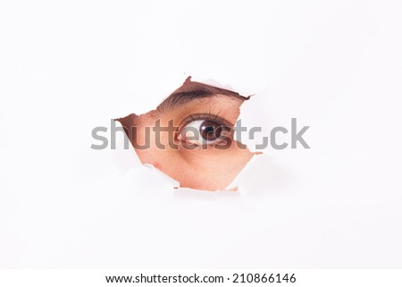A young woman's eye looking through the cracked wall. - stock photo