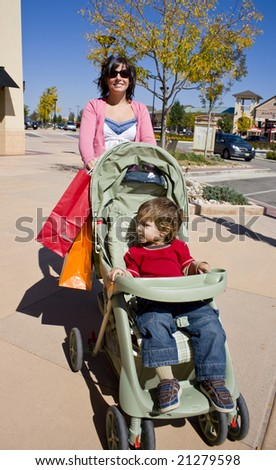 A young woman shopping pushing a stroller holding bags - stock photo